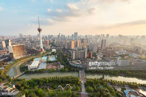 aerial view of city buildings against cloudy sky - chengdu stock pictures, royalty-free photos & images