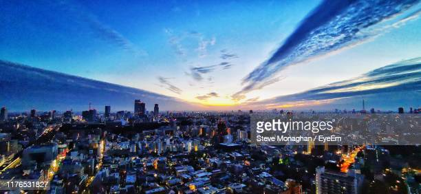 aerial view of city buildings against sky during sunset - 薄明かり ストックフォトと画像
