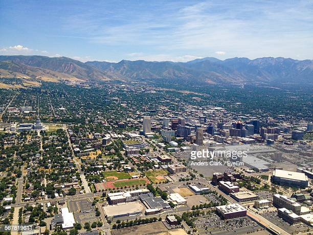 Aerial View Of City Buildings By Mountains Against Cloudy Sky