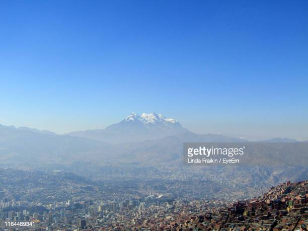 aerial view of city by mountains against clear blue sky - linda fraikin stock pictures, royalty-free photos & images