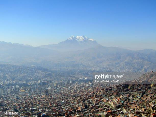 aerial view of city by mountains against clear sky - linda fraikin stock pictures, royalty-free photos & images
