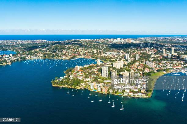 aerial view of city by sea against clear sky - physische geographie stock-fotos und bilder