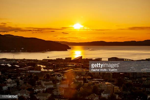 aerial view of city by sea against orange sky - rachel wolfe stock pictures, royalty-free photos & images