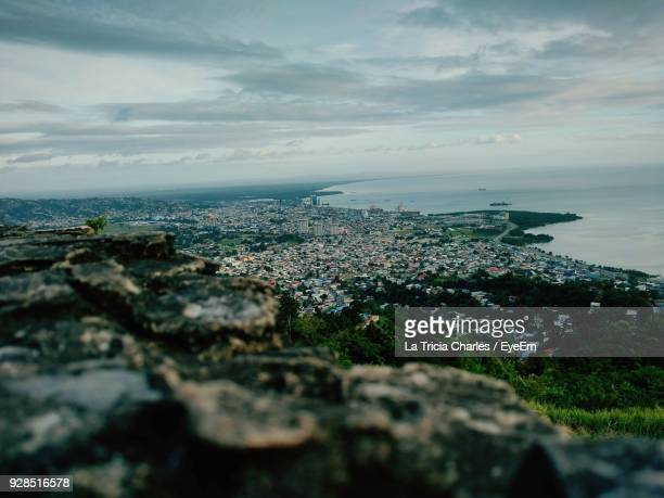 aerial view of city by sea against sky - port of spain stock photos and pictures