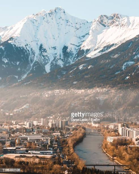 aerial view of city by snowcapped mountains - innsbruck stock pictures, royalty-free photos & images
