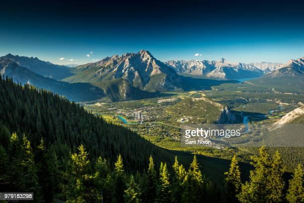 aerial view of city in valley at foot of mountains, banff, alberta, canada - ロッキー山脈 ストックフォトと画像