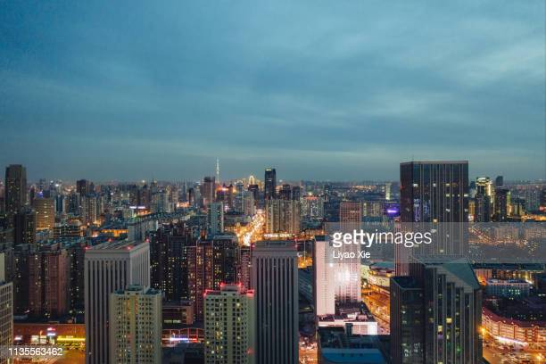 aerial view of city lit up at night - liyao xie photos et images de collection