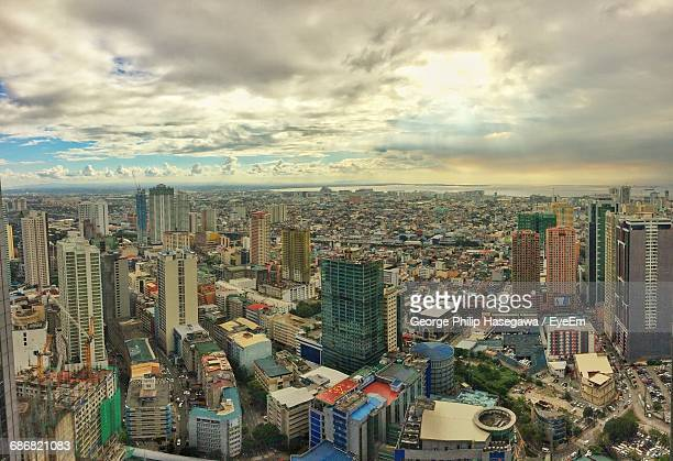 aerial view of cityscape against cloudy sky - makati stock photos and pictures