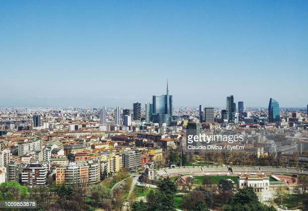 aerial view of cityscape against sky during sunny day - orizzonte urbano foto e immagini stock