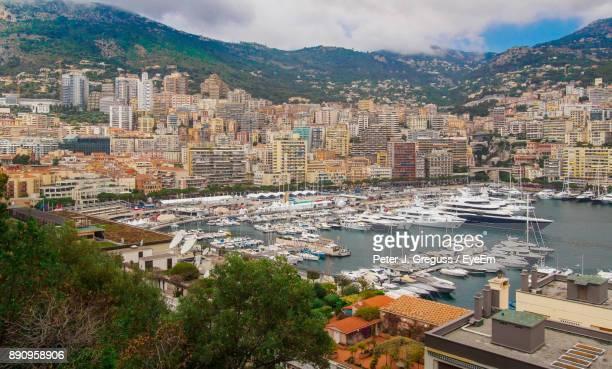Aerial View Of Cityscape By Boats Moored At Sea Against Sky