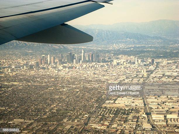 Aerial View Of Cityscape With Cropped Airplane Wing