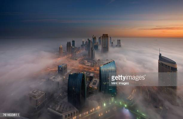 Aerial view of cityscape with illuminated skyscrapers above the clouds in Dubai, United Arab Emirates at dusk.