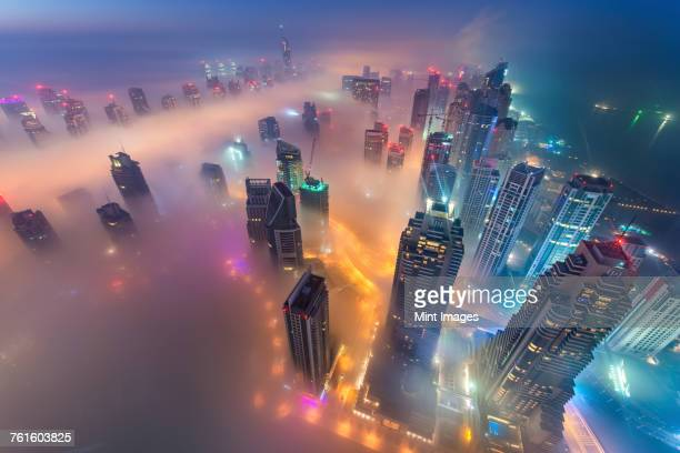 aerial view of cityscape with illuminated skyscrapers above the clouds in dubai, united arab emirates at dusk. - majestuoso fotografías e imágenes de stock