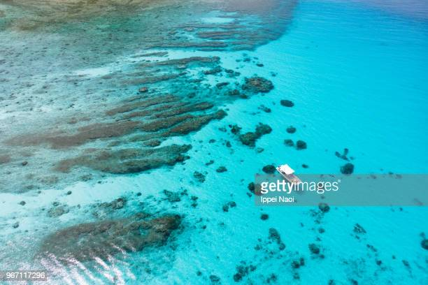 Aerial view of clear blue tropical lagoon with boat and coral reef, Kerama Islands, Okinawa, Japan