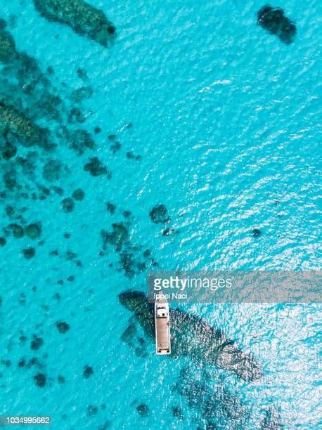 Aerial view of clear blue tropical water and boat, Kerama Islands, Okinawa, Japan
