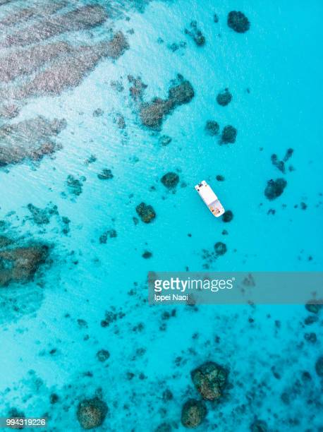 aerial view of clear tropical water, coral reef and boat, kerama islands national park, okinawa, japan - okinawa prefecture stock pictures, royalty-free photos & images