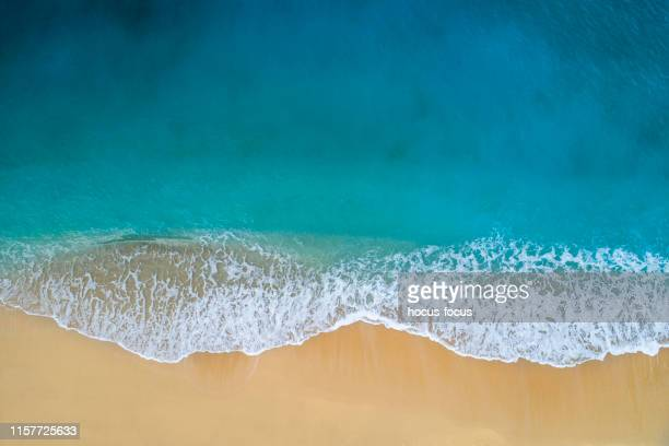 aerial view of clear turquoise sea and waves - riva dell'acqua foto e immagini stock