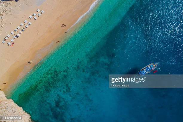 aerial view of clear turquoise sea and yacht - kas stock pictures, royalty-free photos & images