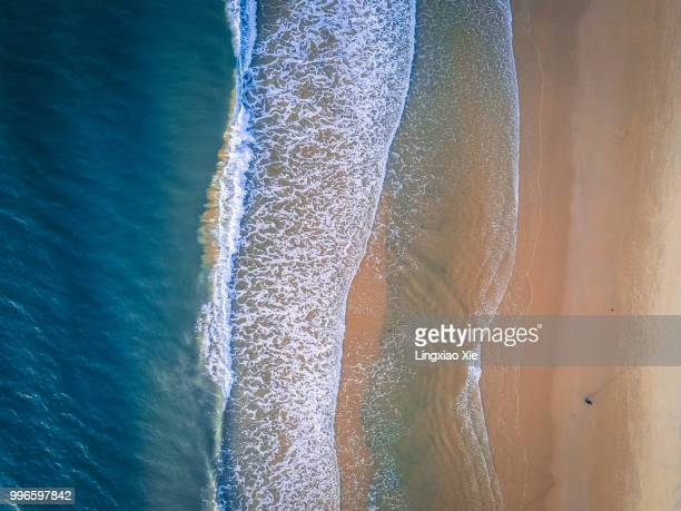 Aerial view of coastline with beach and ocean waves, taken by drone