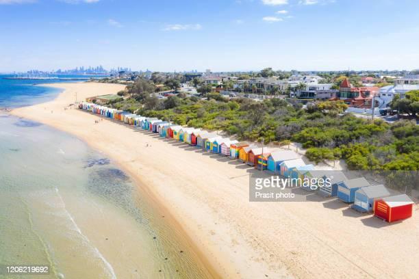 aerial view of colorful brighton bathing boxes on white sandy beach at brighton beach with city in background in melbourne, victoria, australia. - melbourne australia stockfoto's en -beelden