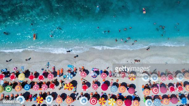 aerial view of colorful umbrellas on shore at beach - albania stock-fotos und bilder