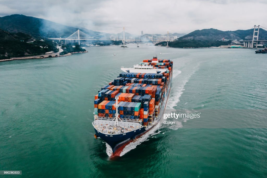 Aerial view of container ship transporting goods sailing across ocean leaving the port : Stock Photo