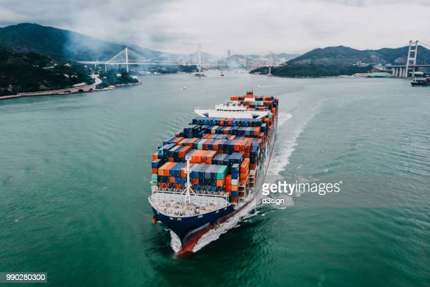 aerial view of container ship transporting goods sailing across ocean leaving the port - cargo ship stock pictures, royalty-free photos & images