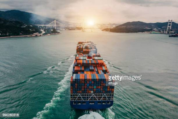 aerial view of container ship transporting goods sailing across ocean entering the port - schiff stock-fotos und bilder