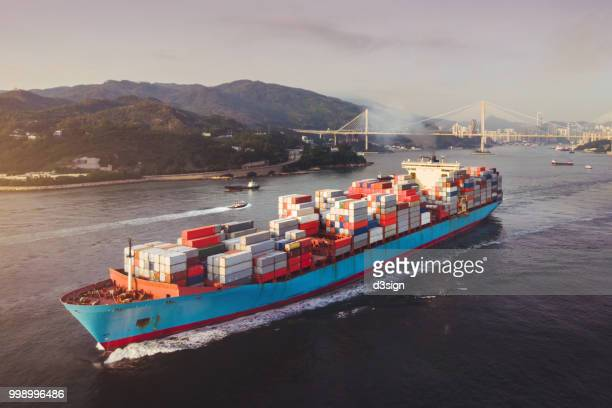 Aerial view of container ship transporting goods sailing across ocean leaving the port