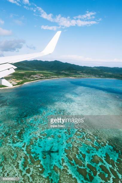 Aerial view of coral reefs with airplane shadow, Ishigaki Island, Japan