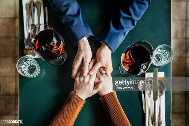 aerial view of couple holding hands at restaurant table - love stock pictures, royalty-free photos & images