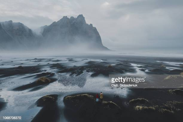 aerial view of couple looking at   vestrahorn mountains near the sea - dramatic landscape stock pictures, royalty-free photos & images