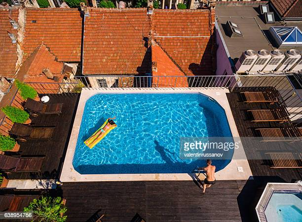 Aerial view of couple relaxing in rooftop swimming pool