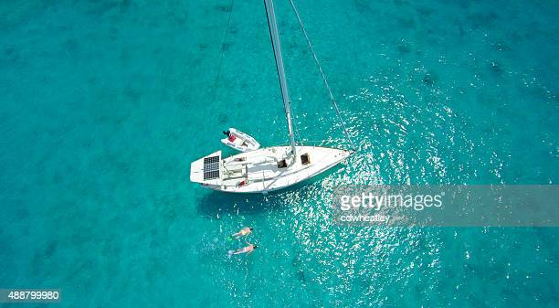 aerial view of couple snorkeling by sailboat in the Caribbean