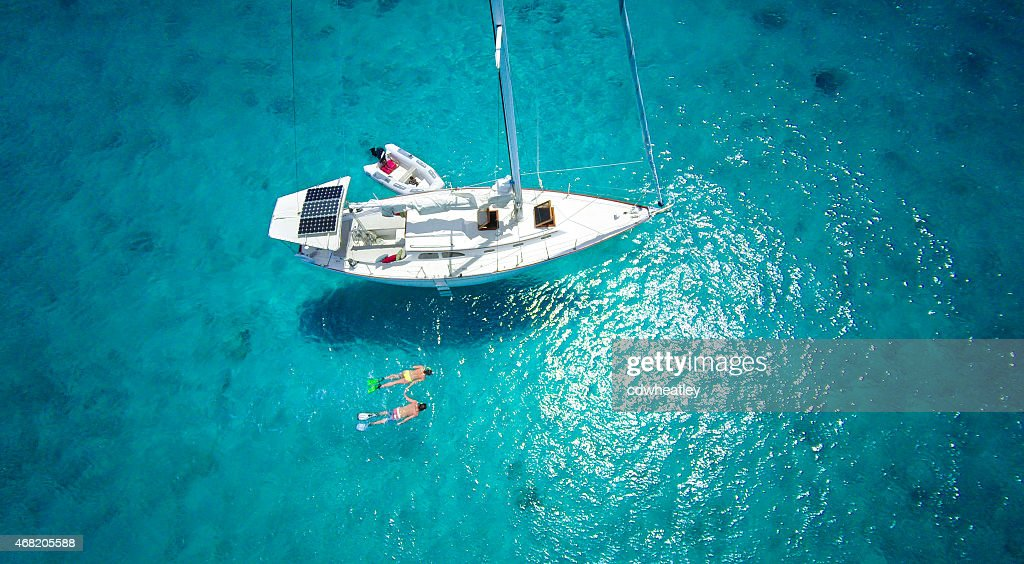 aerial view of couple snorkeling next to a luxury sailboat : Stock Photo