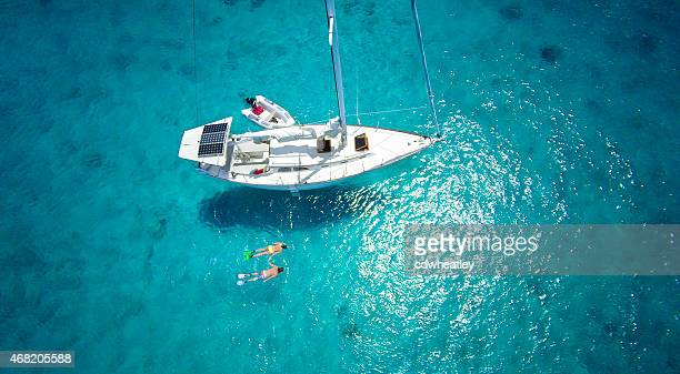 aerial view of couple snorkeling next to a luxury sailboat - small boat stock pictures, royalty-free photos & images