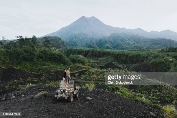 aerial view of couple standing   old fashioned suv on the background of merapi volcano - volcanic terrain stock pictures, royalty-free photos & images