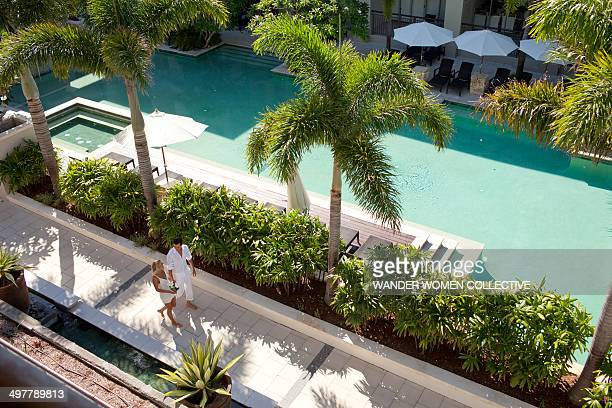 aerial view of couple waking around resort pool - sport venue stock pictures, royalty-free photos & images