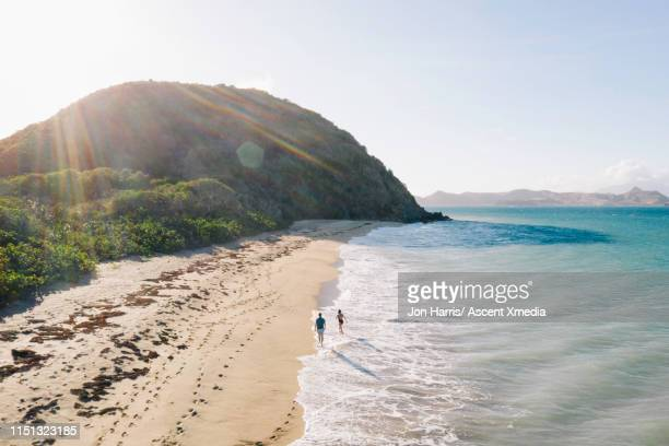 aerial view of couple walking along beach - idyllic stock pictures, royalty-free photos & images