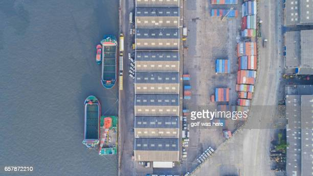 Aerial view of cranes unloading container ship at commercial dock