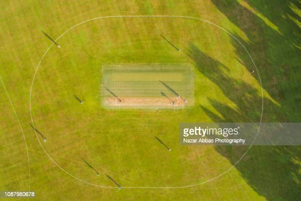 aerial view of cricket game. - cricket pitch stock pictures, royalty-free photos & images