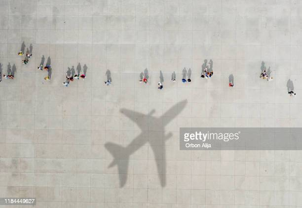 aerial view of crowd with airplane shadow - airport tarmac stock pictures, royalty-free photos & images