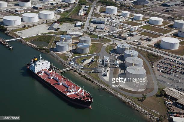 aerial view of crude oil tanker and storage tanks - storage tank stock photos and pictures