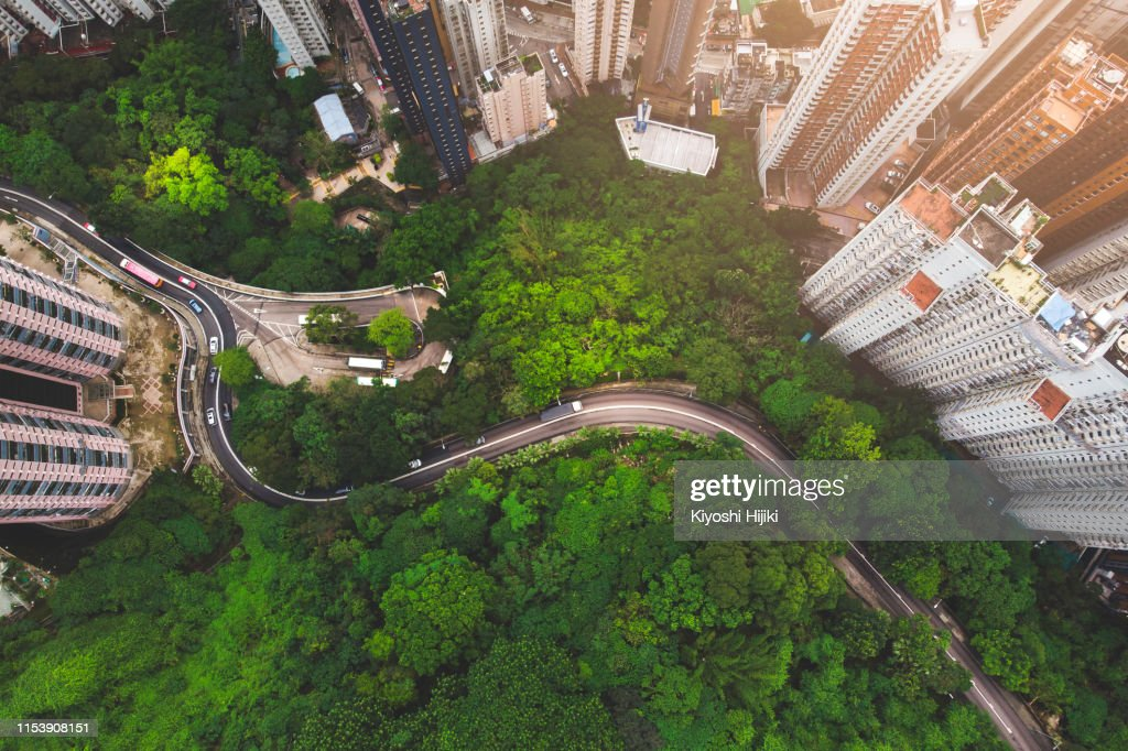 Aerial view of curve road in forest against buildings in Hong Kong : Stock Photo