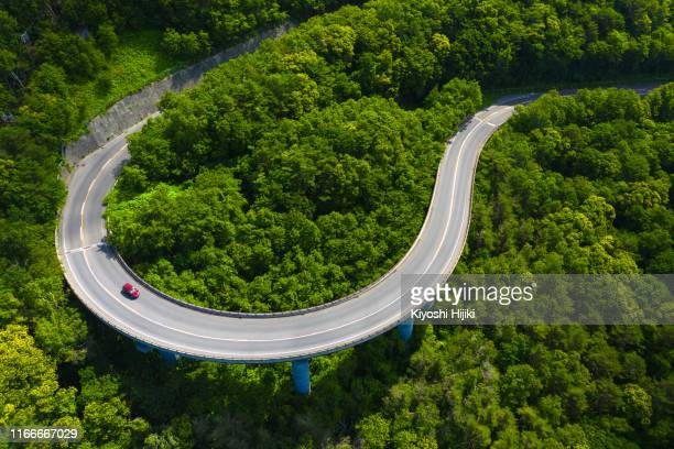 aerial view of curve road through green forest on mountain in summer - land vehicle stock pictures, royalty-free photos & images