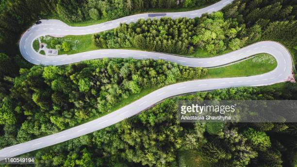 aerial view of curvy mountain road in austrian alps - mountain road stock pictures, royalty-free photos & images