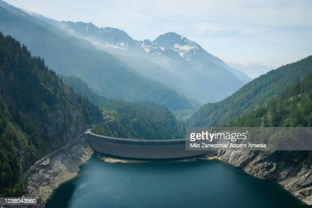 aerial view of dam and reservoir in a mountainous valley - stausee stock-fotos und bilder