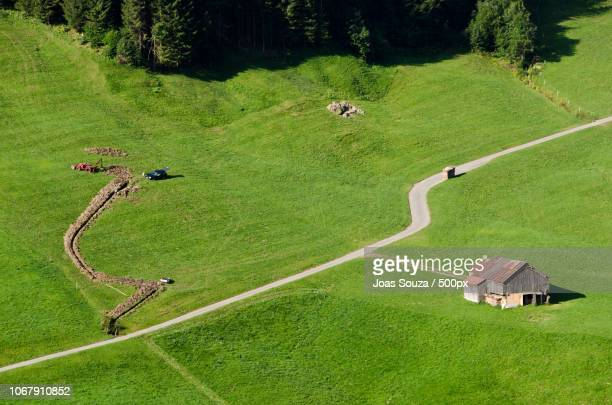 Aerial view of digging earth mover, road, meadow and old building