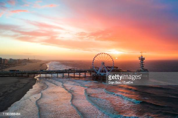 aerial view of ferris wheel against sea and sky during sunset - ハーグ ストックフォトと画像