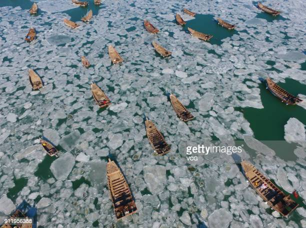 Aerial view of fishing vessels sitting frozen on icy Golden Pebble Beach on January 24 2018 in Dalian Liaoning Province of China Fishermen halted...